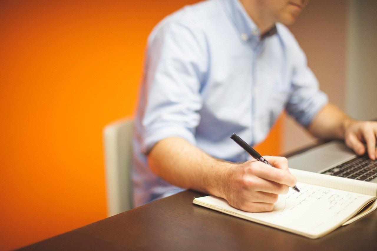 man sitting at desk creating personal marketing plan